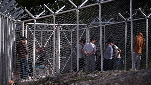 Migrants stand behind a fence at the VIAL detention center on the island of Chios where migrants and refugees arrived after the March 20 EU-Turkey deal are kept, on April 4, 2016 - Sputnik International