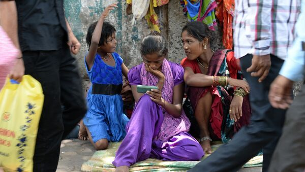 An Indian pavement dweller watches a movie on a mobile phone as others interact in Mumbai on June 3, 2015 - Sputnik International