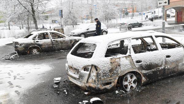 A policeman investigates a burnt car in the Rinkeby suburb outside Stockholm, Sweden February 21, 2017 - Sputnik International
