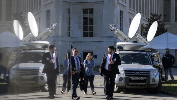 People walk past trucks with satellite dish on the eve of resumption of peace talks on Syria, on February 22, 2017 at the United Nations offices in Geneva - Sputnik International