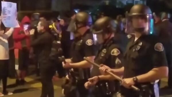 Police stand guard as demonstrators protests an off-duty LAPD officers firing his weapon at an unarmed teenage boy. - Sputnik International