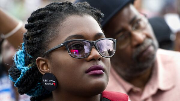 A young woman wears earrings with the slogan Black Lives Matter printed on them during the dedication and opening ceremony of the Smithsonian's National Museum of African American History and Culture in Washington, Saturday, Sept. 24, 2016. - Sputnik International