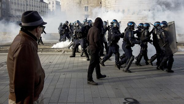A man looks at riot police throwing tear gas while protesters demonstrate against the visit of French presidential election candidate for the far-right Front National (FN) party, on February 25, 2017 in Nantes, western France. - Sputnik International