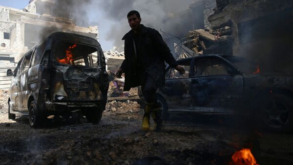 A civil defence member works amid burning vehicles at a site hit by airstrikes in the rebel held besieged Douma neighbourhood of Damascus, Syria, February 26, 2017. - Sputnik International