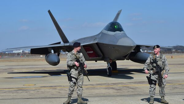 US soldiers stand guard near a US F-22 stealth fighter at the Osan Air Base in Pyeongtaek, south of Seoul, on February 17, 2016. - Sputnik International