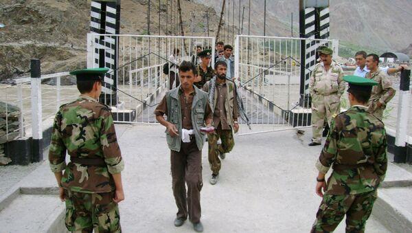 Tajik border guards checking identification documents of people crossing the Tajik-Afghan border on a bridge across the Panj River outside the city of Panj - Sputnik International
