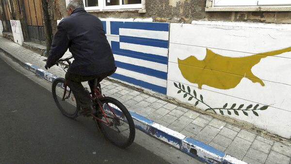 A man passes with a bicycle outside of a Greek Cypriot guard post with Cyprus', right, and Greece' flags painted on the wall in central divided capital Nicosia in the eastern Mediterranean island of Cyprus, on Thursday, Feb. 16, 2017 - Sputnik International