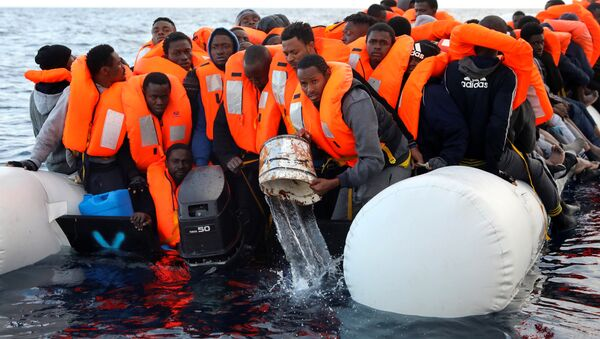 Sub-saharan migrants are seen aboard an overcrowded raft, as one of them uses a bucket to remove water from the raft, during a rescue operation by the Spanish NGO Proactiva Open Arms in the central Mediterranean Sea, north of the coastal Libyan city of Sabratha, February 3, 2017 - Sputnik International