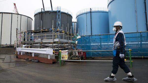 A Tokyo Electric Power Co.'s (TEPCO) employee walks past storage tanks for contaminated water at the company's Fukushima Dai-ichi nuclear power plant in Okuma, Fukushima, Japan, on February 23, 2017 - Sputnik International