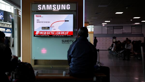 Passengers watch a television broadcasting a news report on North Korea firing ballistic missiles, at a railway station in Seoul, South Korea, March 6, 2017. - Sputnik International