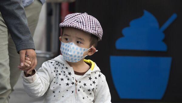 A child walks past a dessert stand during a hazy day in Beijing Friday, Oct. 14, 2016. - Sputnik International