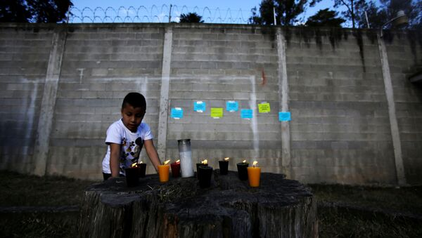 Candles are lit for victims after a fire broke out at the Virgen de Asuncion home in San Jose Pinula on the outskirts of Guatemala City, March 8, 2017 - Sputnik International