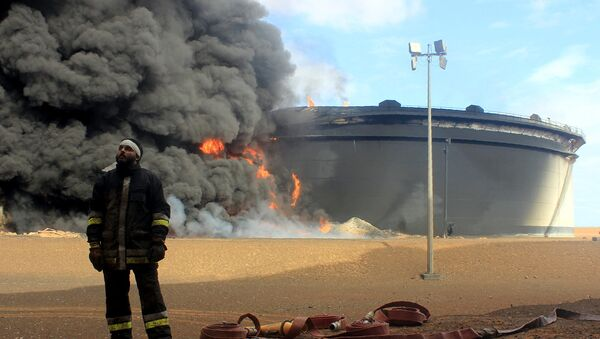 A Libyan fireman stands in front of smoke and flames rising from an oil storage tank at an oil facility in northern Libya's Ras Lanouf region on January 23, 2016, after it was set ablaze earlier in the week following attacks launched by Islamic State (IS) group jihadists to seize key port terminals. - Sputnik International