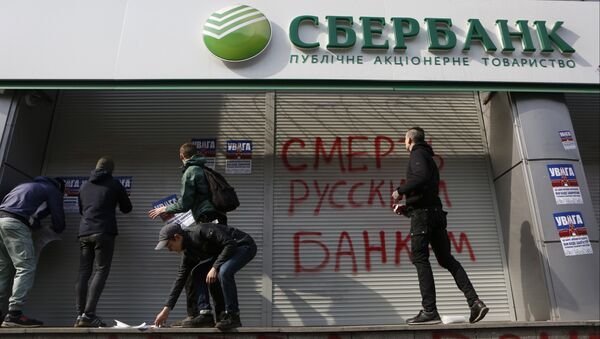 Radicals in front of a Sberbank branch in Kiev, putting up posters which read Attention! This is a bank of an aggressor country. It will be closed. Urgently withdraw your money!, during a protest. Graffiti reads Death to Russian banks. March 10, 2017 - Sputnik International