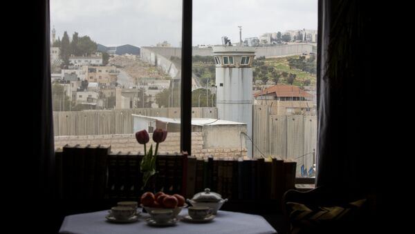 An Israeli security watch tower is seen from one of the rooms of the The Walled Off Hotel in the West Bank city of Bethlehem, Friday, March 3, 2017. - Sputnik International