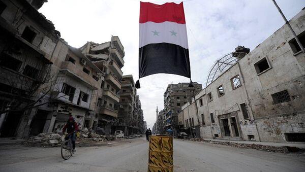A Syrian national flag hangs in a damaged neighbourhood in Aleppo, Syria - Sputnik International