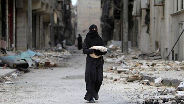 Syrian woman walks past a destroyed building in Aleppo - Sputnik International
