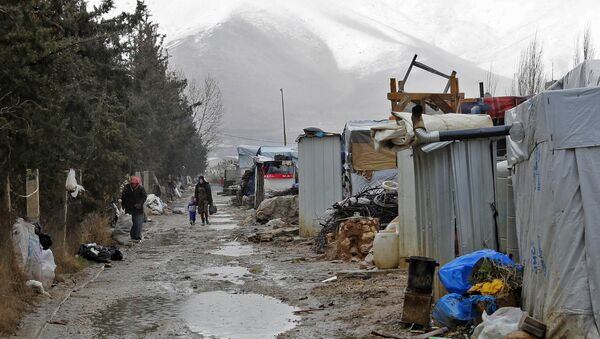 Syrian refugees walking at an unofficial refugee camp near a snow covered mountain in the village of Deir Zannoun in Lebanon's Bekaa valley. - Sputnik International