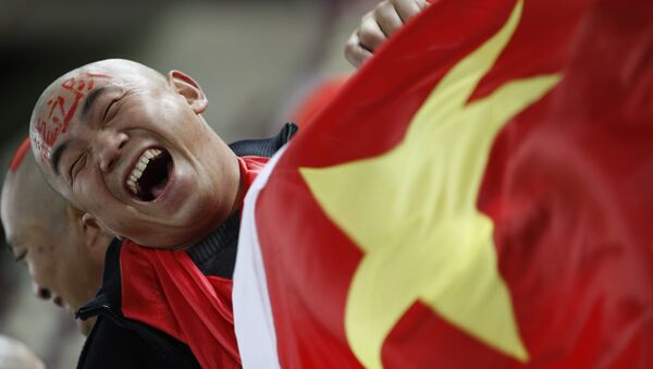 In this Wednesday, Jan. 12, 2011, file photo, a Chinese soccer fan cheers for his team before their AFC Asian Cup group A soccer match against Qatar in Doha, Qatar. - Sputnik International