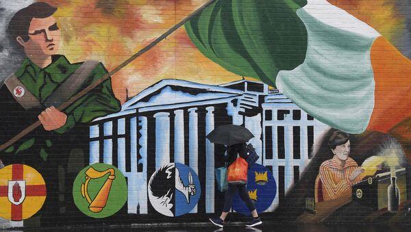 A woman walks past a political mural in the Falls Road area of west Belfast, Northern Ireland, February 28, 2017. - Sputnik International
