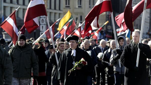 People hold flags, as they participate in the annual procession commemorating the Latvian Waffen-SS (Schutzstaffel) unit, also known as the Legionnaires, in Riga, Latvia March 16, 2017 - Sputnik International