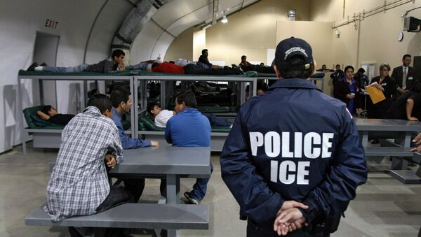An Immigration and Customs Enforcement (ICE) officer guards a group of 116 Salvadorean immigrants that wait to be deported,at Willacy Detention facility in Raymondville, Texas on December 18, 2008 - Sputnik International