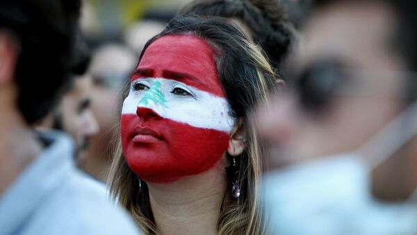 A Lebanese woman, with her face painted in the colours of Lebanon's national flag, takes part in a demonstration in downtown Beirut on August 8, 2015 - Sputnik International