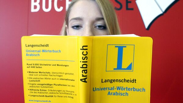 A young woman holds an universal dictionary Arabic as she sits in front of a poster at the International Bookfair in Frankfurt , Germany (File) - Sputnik International