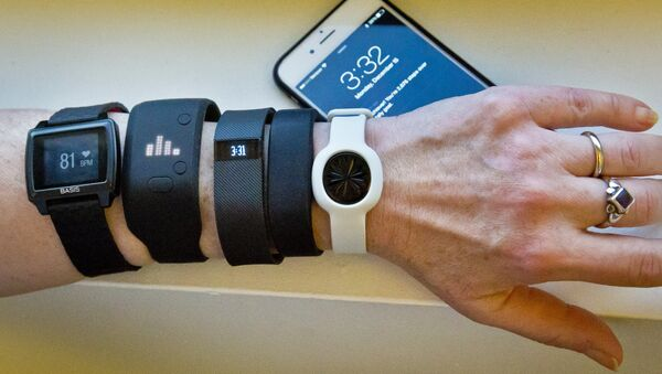 Fitness trackers, from left, Basis Peak, Adidas Fit Smart, Fitbit Charge, Sony SmartBand, and Jawbone Move, are posed for a photo next to an iPhone, in New York (File) - Sputnik International
