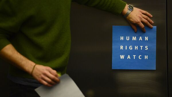 A man puts a logo of US-based rights group Human Rights Watch on the wall as he prepares the room before their press conference to release their annual World report on January 21, 2014 in Berlin - Sputnik International