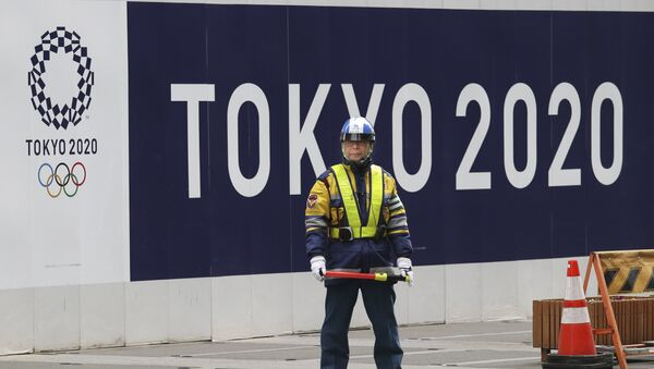 A security guard stands in front of an official logo of the 2020 Tokyo Olympic Games on the safety wall at a construction site in Tokyo's Nihonbashi shopping and office district, Monday, Feb. 6, 2017 - Sputnik International