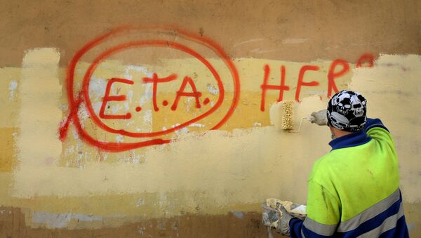 A municipal worker paints over graffiti reading ETA, The People Are With You in the Basque town of Guernica, Spain. - Sputnik International