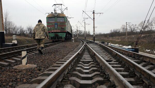 Ukrainian military veteran walks along rails as he takes part in a blockade against ongoing trade with Russian-backed insurgents, on February 23, 2017, in Kryvyi Torets railway station, Donetsk region - Sputnik International