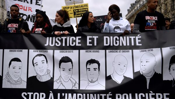 People hold a banner depicting victims of alleged police brutality as they take part in a demonstration called by the families of the victims, LDH, the Mrap, CGT and FSU against police brutality, discrimination and racism in Paris on March 19, 2017 - Sputnik International