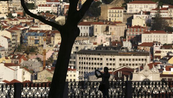 A woman taking pictures from a public garden is silhouetted against the buildings in Lisbon's old town center Wednesday evening, March 15, 2017. - Sputnik International