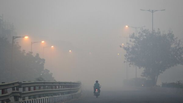 A man rides a scooter on a road enveloped by smoke and smog, on the morning following Diwali festival in New Delhi, India, Monday, Oct. 31, 2016.  - Sputnik International