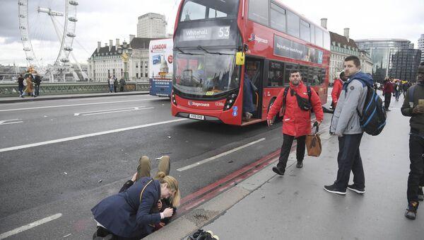 A woman assist an injured person after an incident on Westminster Bridge in London - Sputnik International