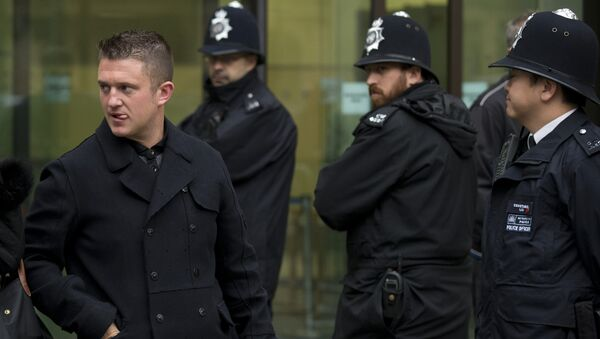 Tommy Robinson, left, the former leader of the far-right EDL English Defence League group walks past police officers as he leaves after an appearance at Westminster Magistrates Court in London, Wednesday, Oct. 16, 2013. - Sputnik International