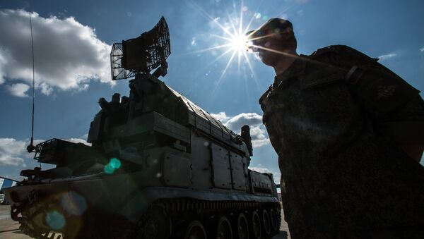 A serviceman is seen near a Tor surface-to-air missile system during preparations for the Engineering Technologies 2014 international forum in Zhukovsky near Moscow - Sputnik International
