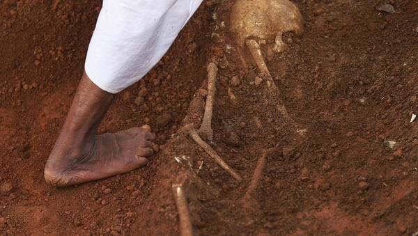 In this Jan 2, 2013 photo, a hospital worker walks by a partially excavated skeleton, at a mass grave found inside the premises of a government hospital in Matale, about 140 kilometers (about 88 miles) north east of Colombo, Sri Lanka. - Sputnik International