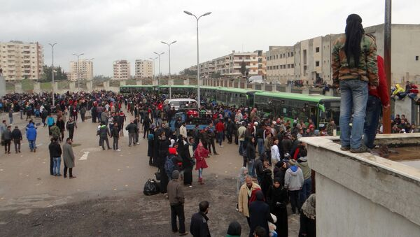 Opposition fighters and their families gather as they prepare to board a bus, ahead of their evacuation from the rebel-held Waer neighbourhood in the central city of Homs on March 18, 2017 - Sputnik International