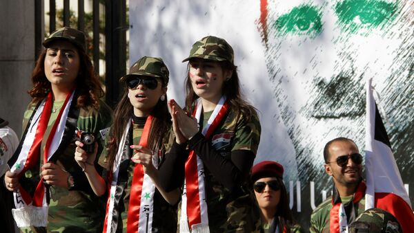 Syrian pro-regime supporters dressed in military uniform stand in front of a mural of President Bashar al-Assad during a rally in Damascus. File photo - Sputnik International