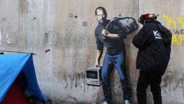 Граффити Бэнкси изображающее Стива Джобса на стене лагеря беженцев во Франции - Sputnik International