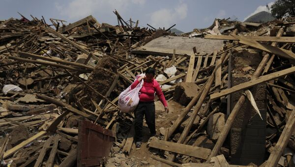 A woman carries her salvaged goods through the rubble of destroyed houses following a massive earthquake in the town of Longtoushan in Ludian County in southwest China's Yunnan Province (File) - Sputnik International