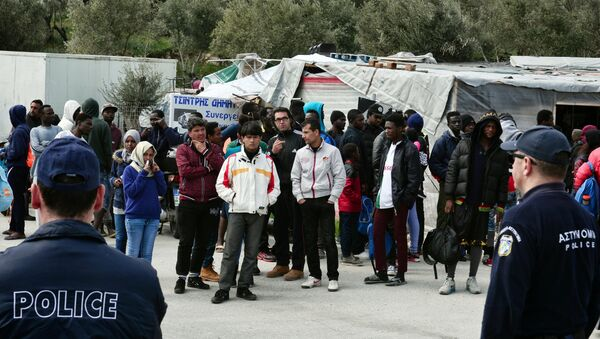 A picture taken on March 16, 2017 shows policemen standing guard near migrants at the Moria migrant camp on the island of Lesbos, almost a year after an EU-Turkey deal - Sputnik International