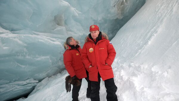 Russian President Vladimir Putin, foreground, and Defense Minister Sergei Shoigu, inspect a cavity in a glacier on the Arctic Franz Josef Land archipelago in Arctic Russia - Sputnik International