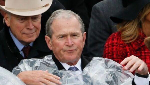 George W. Bush struggles to put on a poncho during Donald Trump's inauguration. - Sputnik International