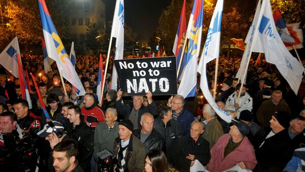 An opposition supporter holds a banner that reads No to war - no to NATO during protest in downtown Podgorica, Montenegro, Saturday, Dec. 12, 2015 - Sputnik International