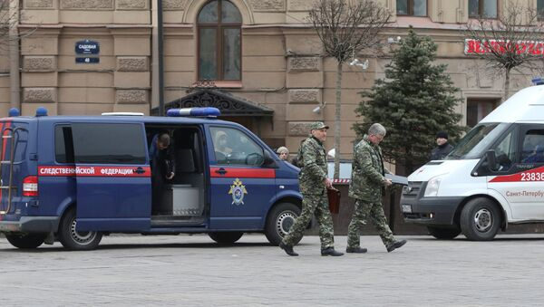 Members of the security services walk past a vehicle of Russia's Investigative Committee outside Sennaya Ploshchad metro station after an explosion tore through a train carriage in the St. Petersburg metro system, in St. Petersburg, Russia April 3, 2017 - Sputnik International