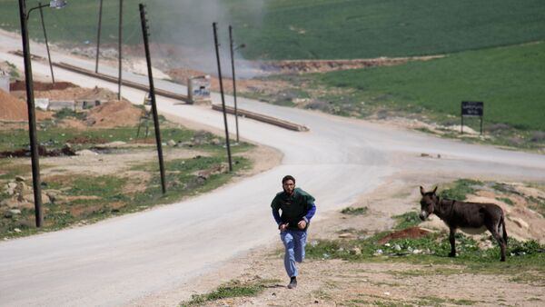 A Syrian medic runs for cover during the air strikes which hit a hospital in Khan Sheikhun, a rebel-held town in the northwestern Syrian Idlib province, on April 4, 2017 - Sputnik International